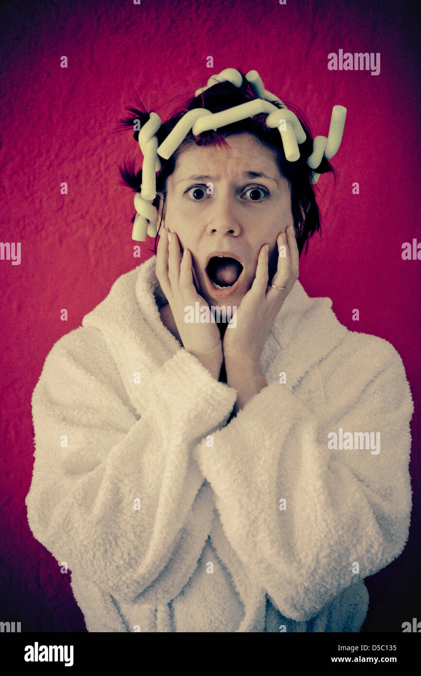 Femme en peignoir et bigoudis Photo Stock