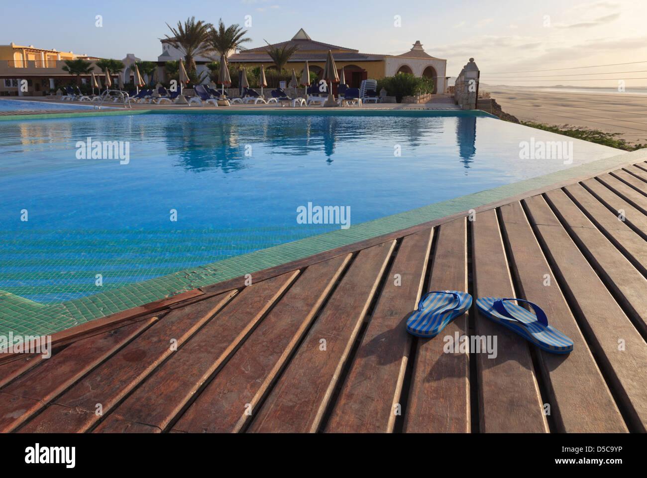 Paire de tongs sur sun decking - terrasse piscine à débordement par du vide dans des vacances de luxe Photo Stock