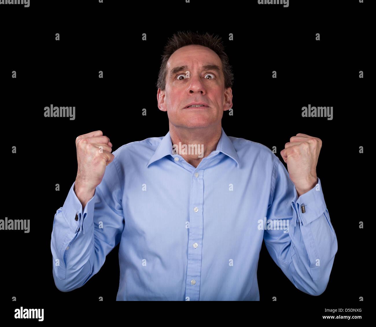 L'âge moyen frustré Business Man Shaking poings de colère Fond noir Photo Stock