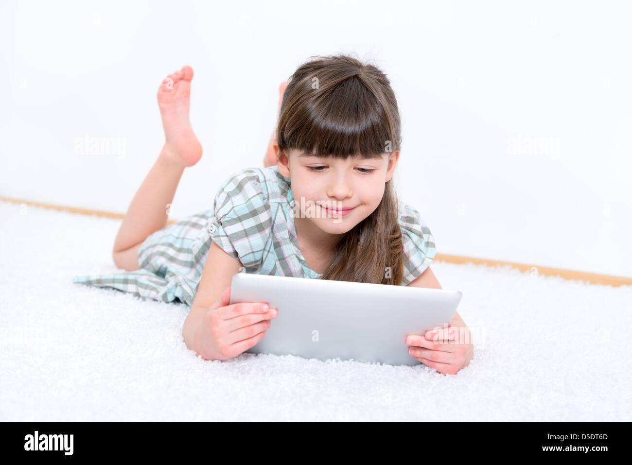 Jeune fille (6-7 ans) à la recherche et à jouer avec une tablette numérique en salle blanche. Photo Stock