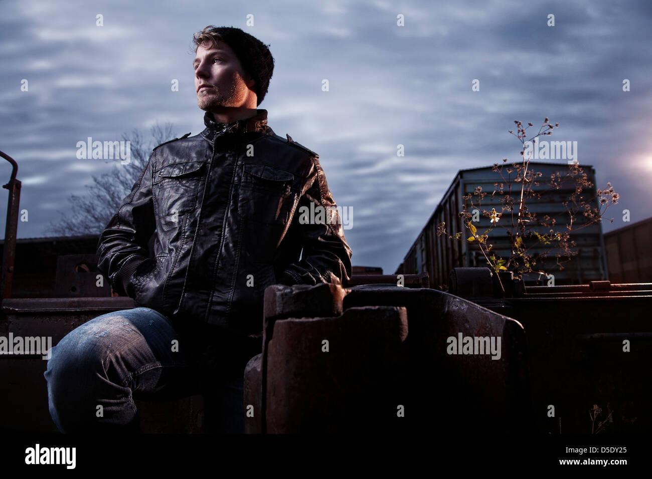 Homme debout en cour de route de rail contre ciel orageux Photo Stock