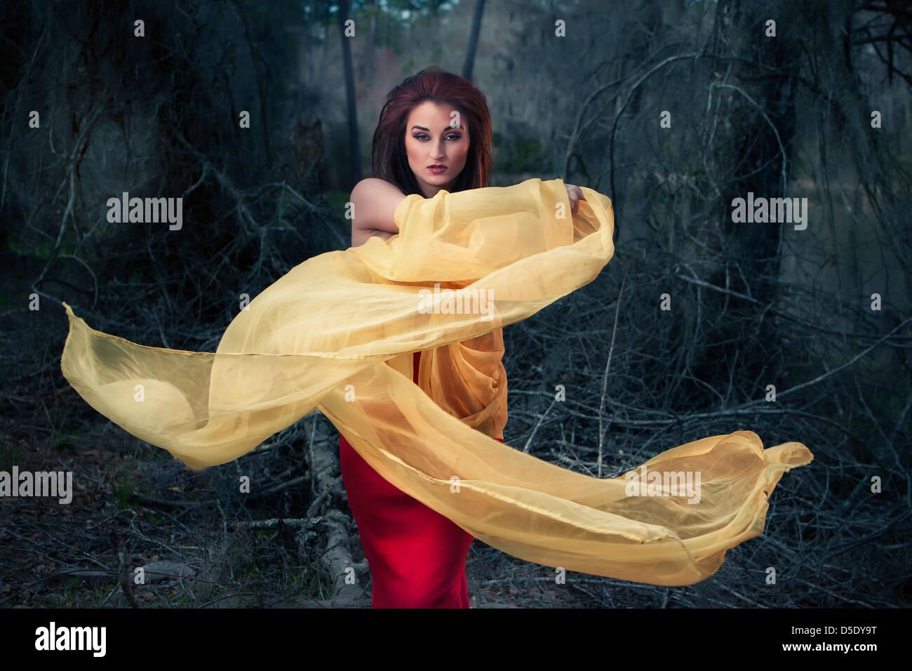 Femme chiffon jaune tourbillonnant dans les bois Photo Stock