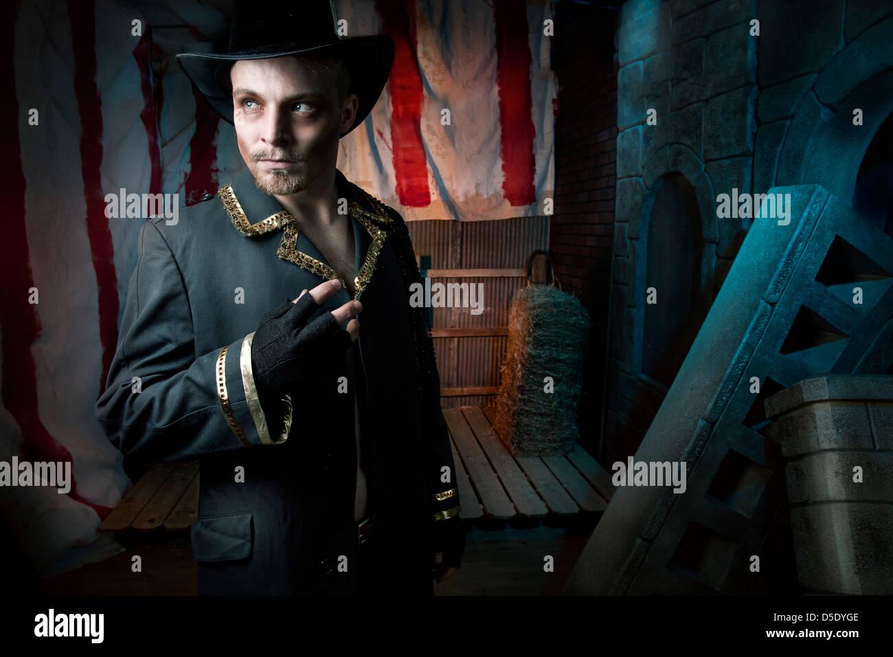 Homme avec top hat in dark tented alley Photo Stock