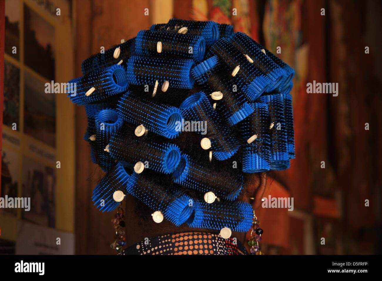 Une femme africaine avec ses cheveux dans un bleu lumineux bigoudis Photo Stock