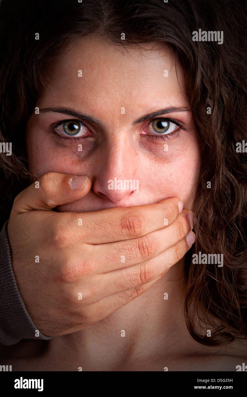 Un gros plan du mans part couvrant une bouche de femme. Concept de la violence domestique ou l'enlèvement. Photo Stock