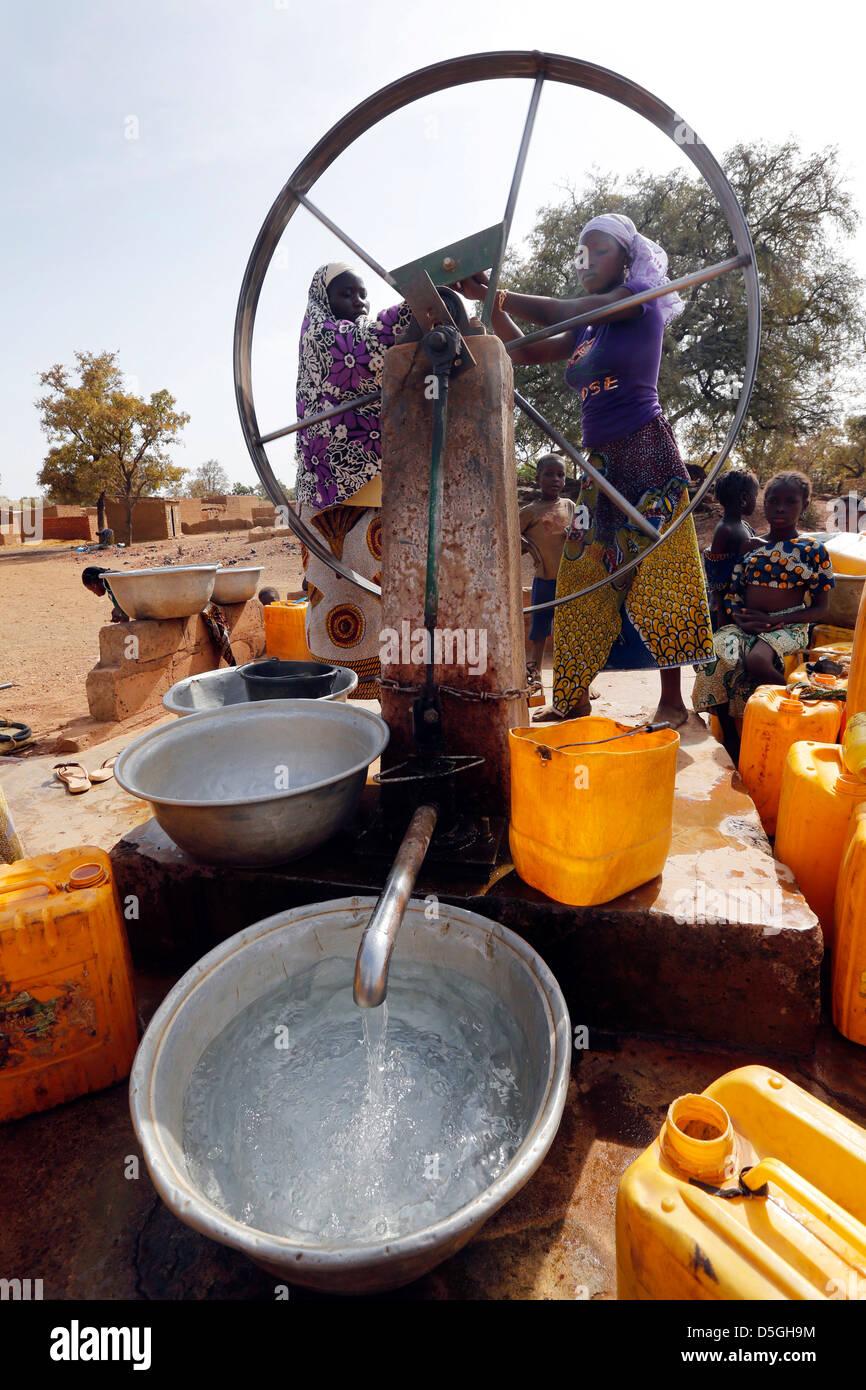 Les femmes tourner la roue d'une pompe à eau dans un village, le Burkina Faso, l'Afrique Photo Stock