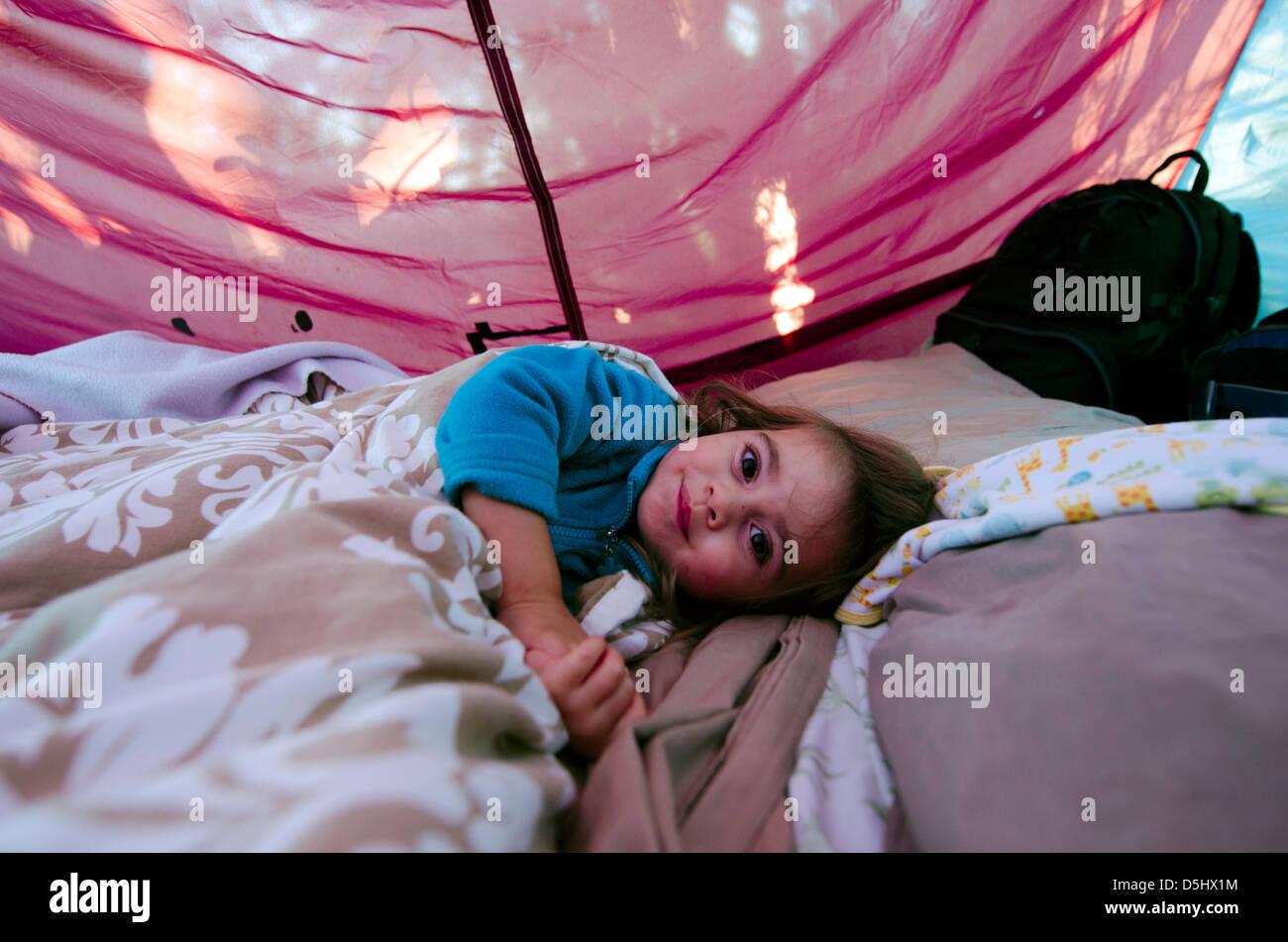 Petite fille à l'intérieur d'une tente de camping se trouvant heureux sur sac de couchage. Photo Stock