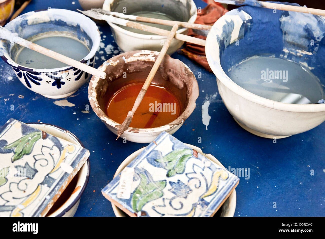 Table de travail de peintre avec des pigments dans des bols Uriarte Talavera Talavera rejeté factory fondée Photo Stock