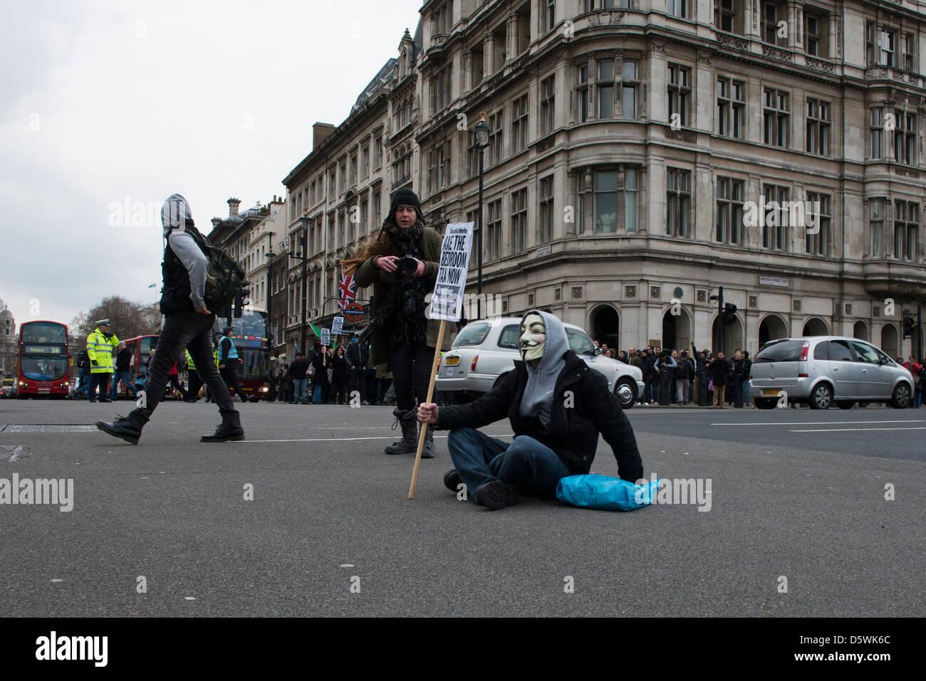 Un manifestant solitaire est assis au milieu d'une route dans la région de Westminster, Londres le 30/03/13 Photo Stock