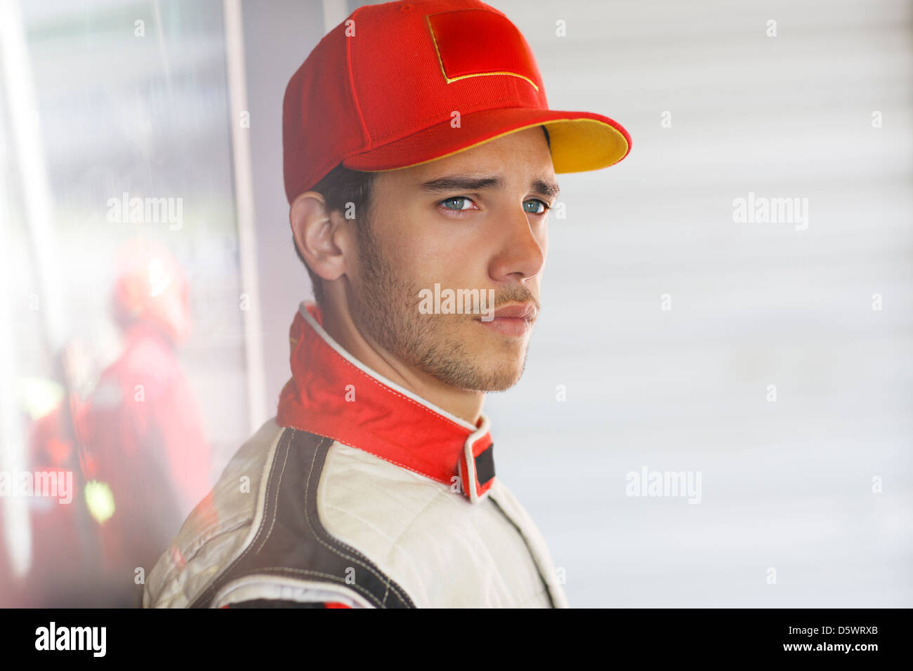 Racer standing in garage Photo Stock