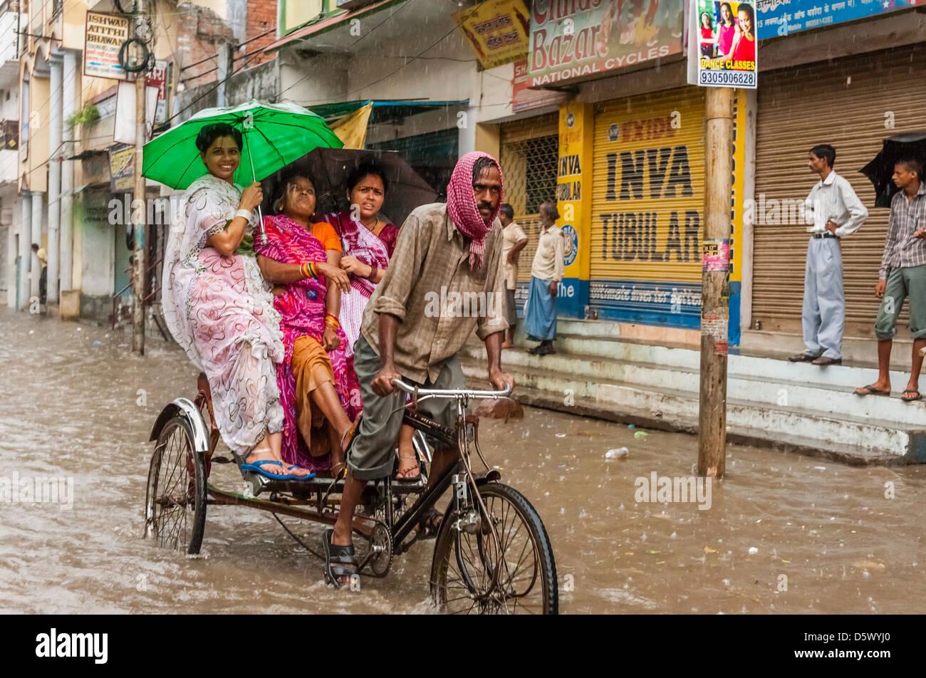 Trois femmes passagers et un cycle rickshaw se flétrissent la tempête pendant la mousson les crues éclair Photo Stock