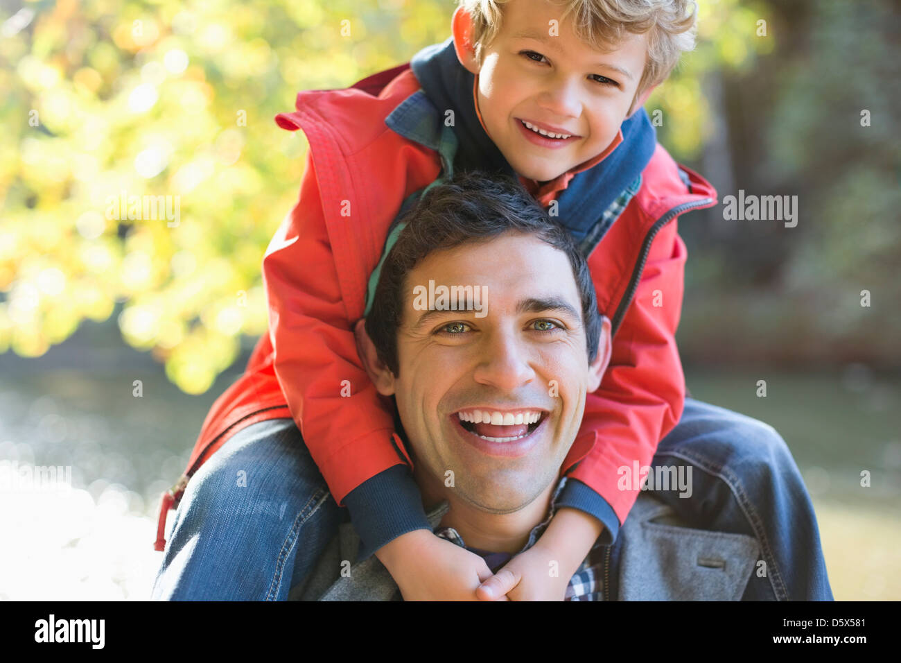 Father carrying son on shoulders in park Banque D'Images