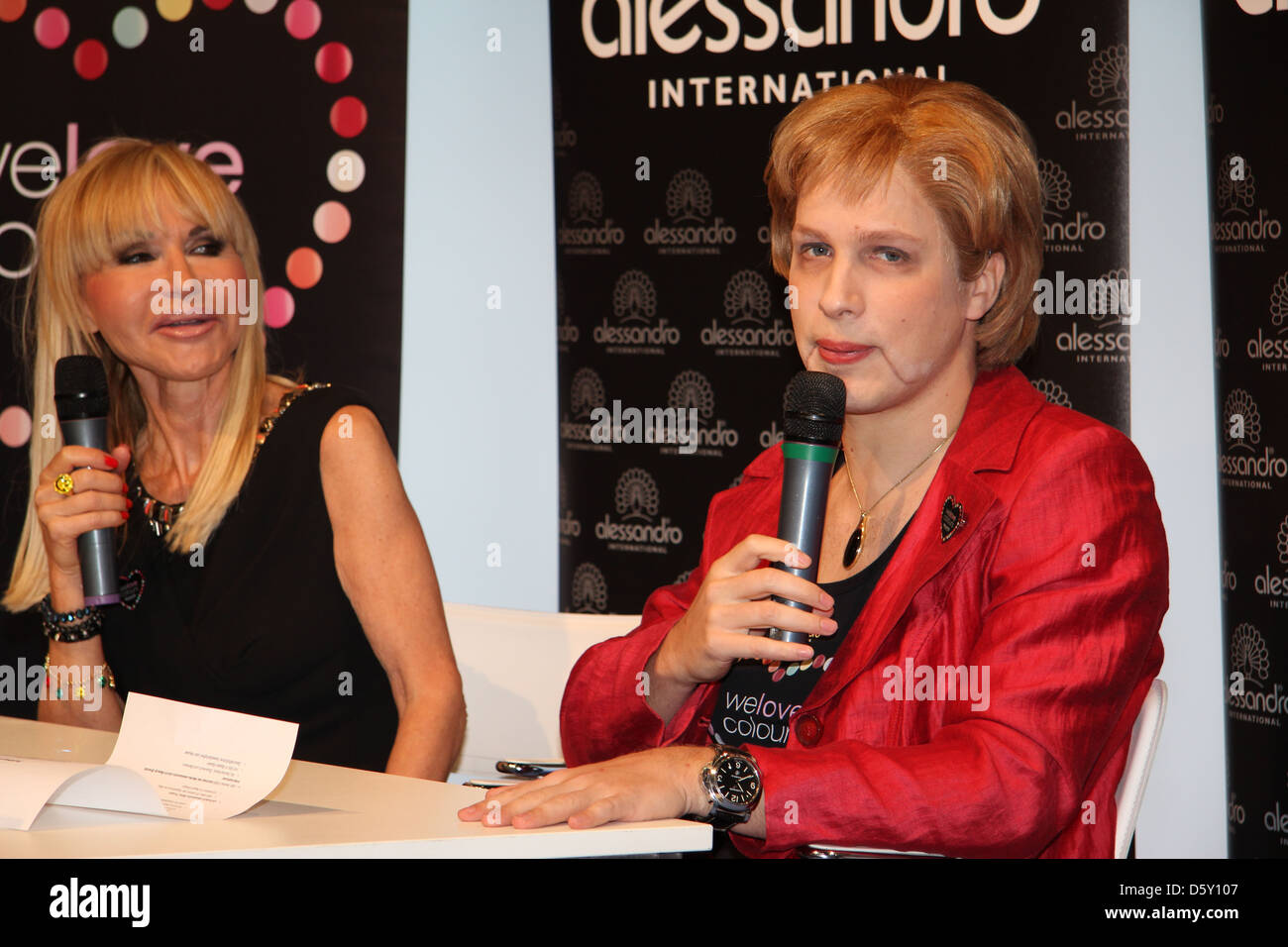 Silvia Troska et Oliver Pocher comme Angela Merkel Salon International de beauté le stand d'Alessandro. Photo Stock