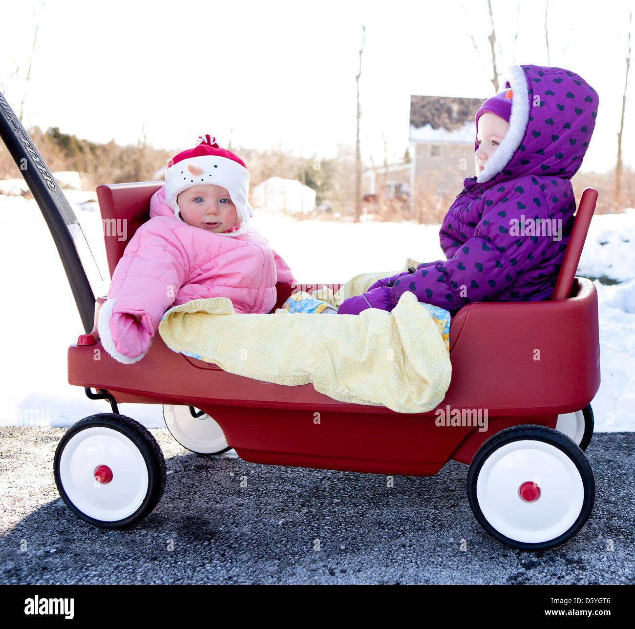 Fille avec petite Sœur assis dans Toy chariot Push Banque D'Images