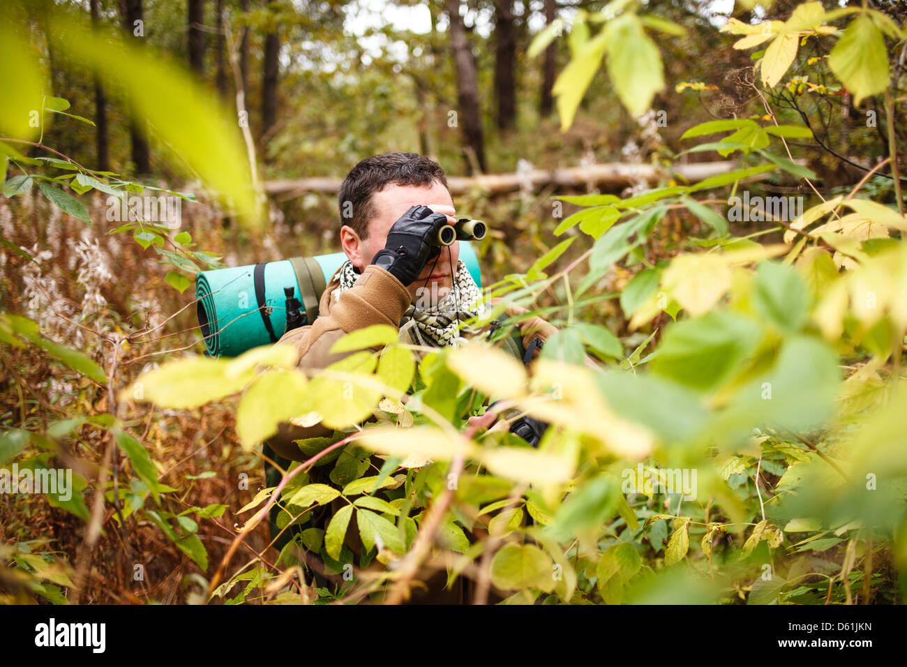 L'homme avec des jumelles à une jungle. Photo Stock