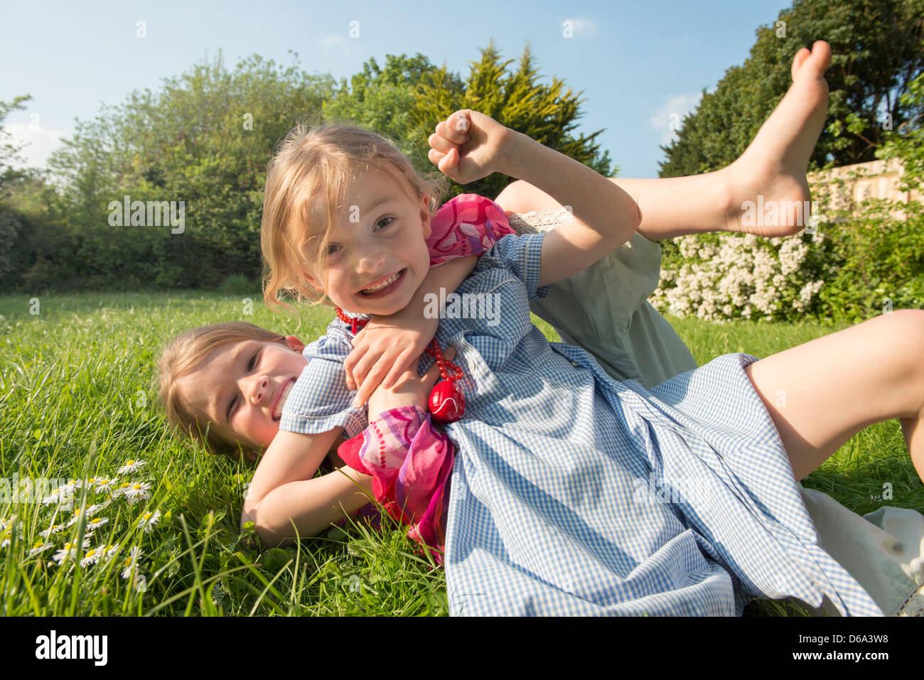 Les filles jouent ensemble in grassy field Photo Stock
