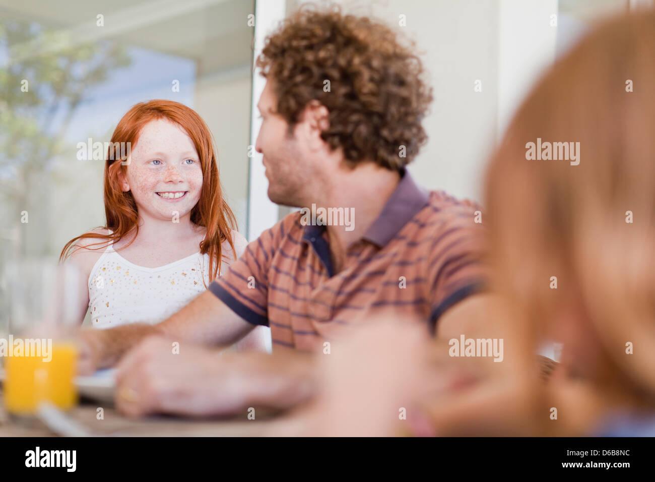 Girl smiling au père au petit déjeuner Photo Stock