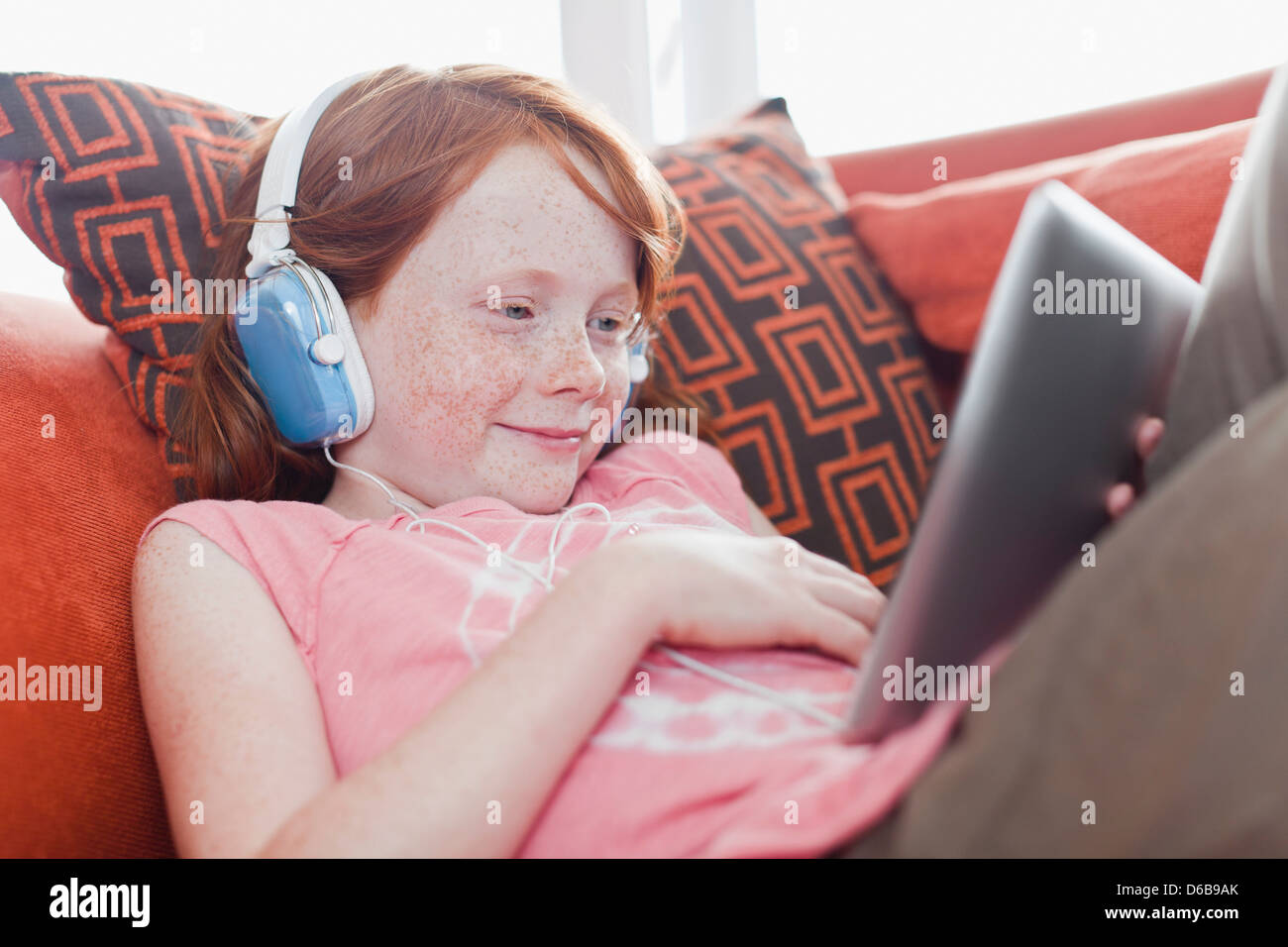 Girl in headphones using tablet computer Photo Stock