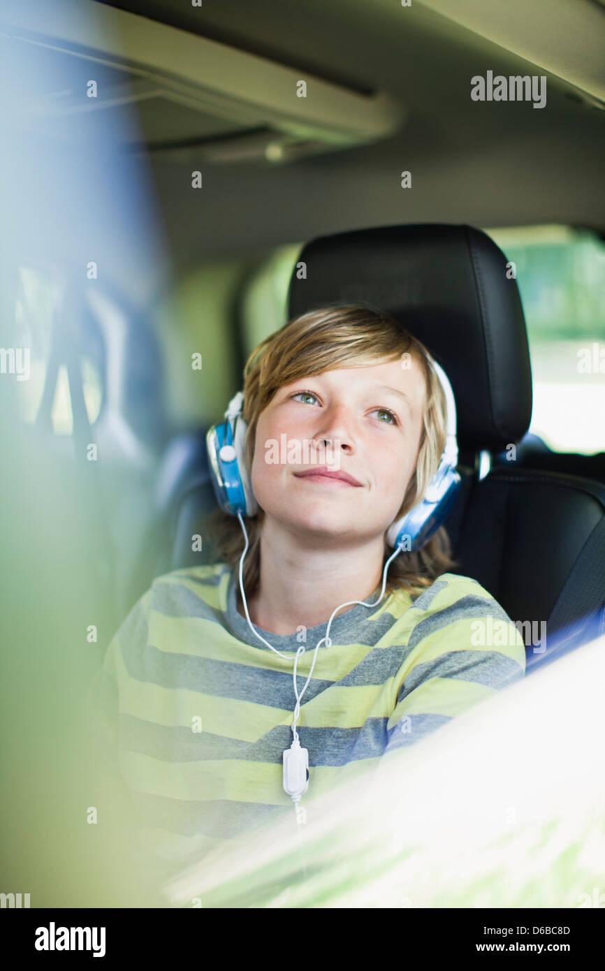 Boy listening to headphones in car Photo Stock