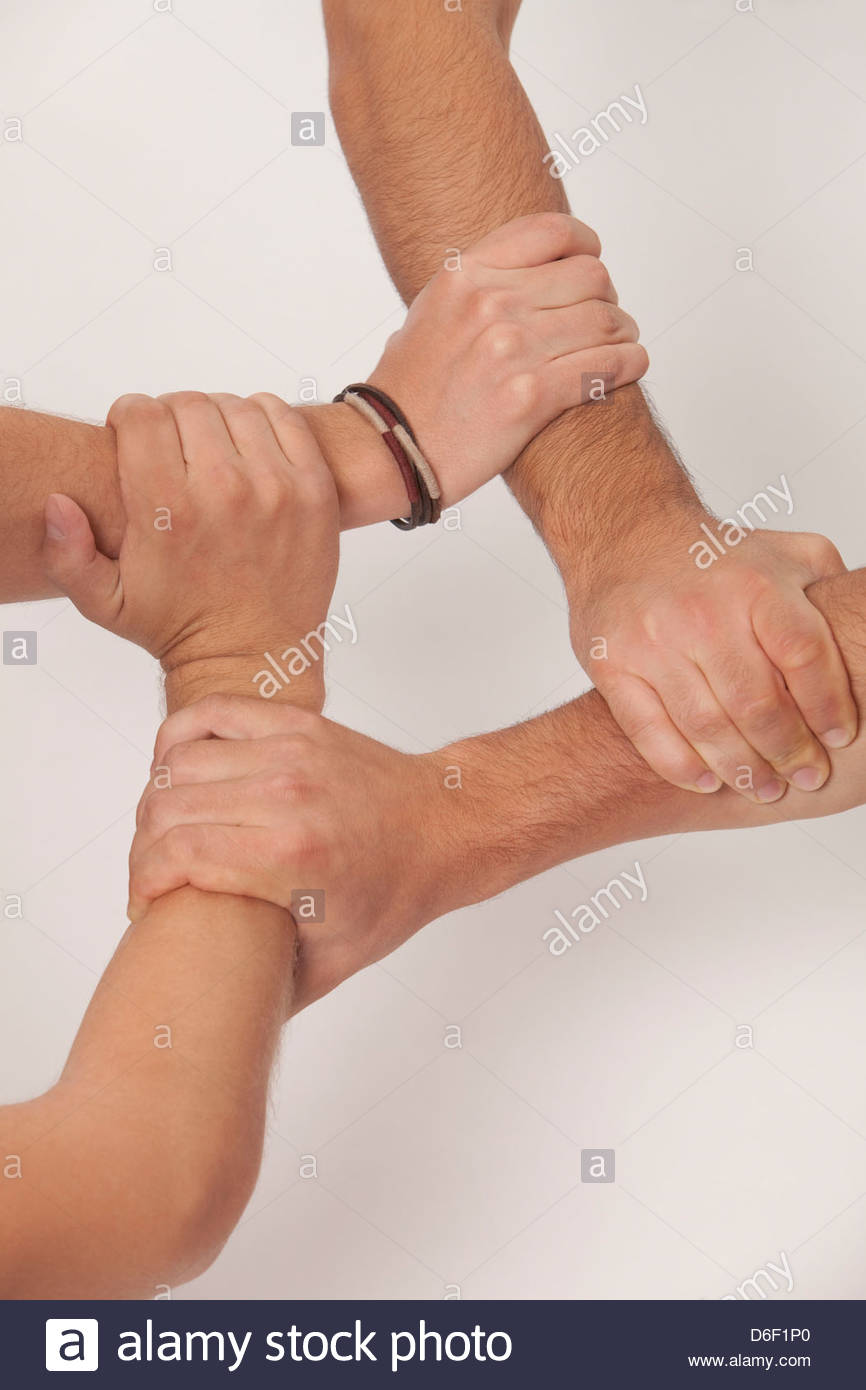 Les mains liées la tenue d'équipe confiance quatre adolescents Photo Stock