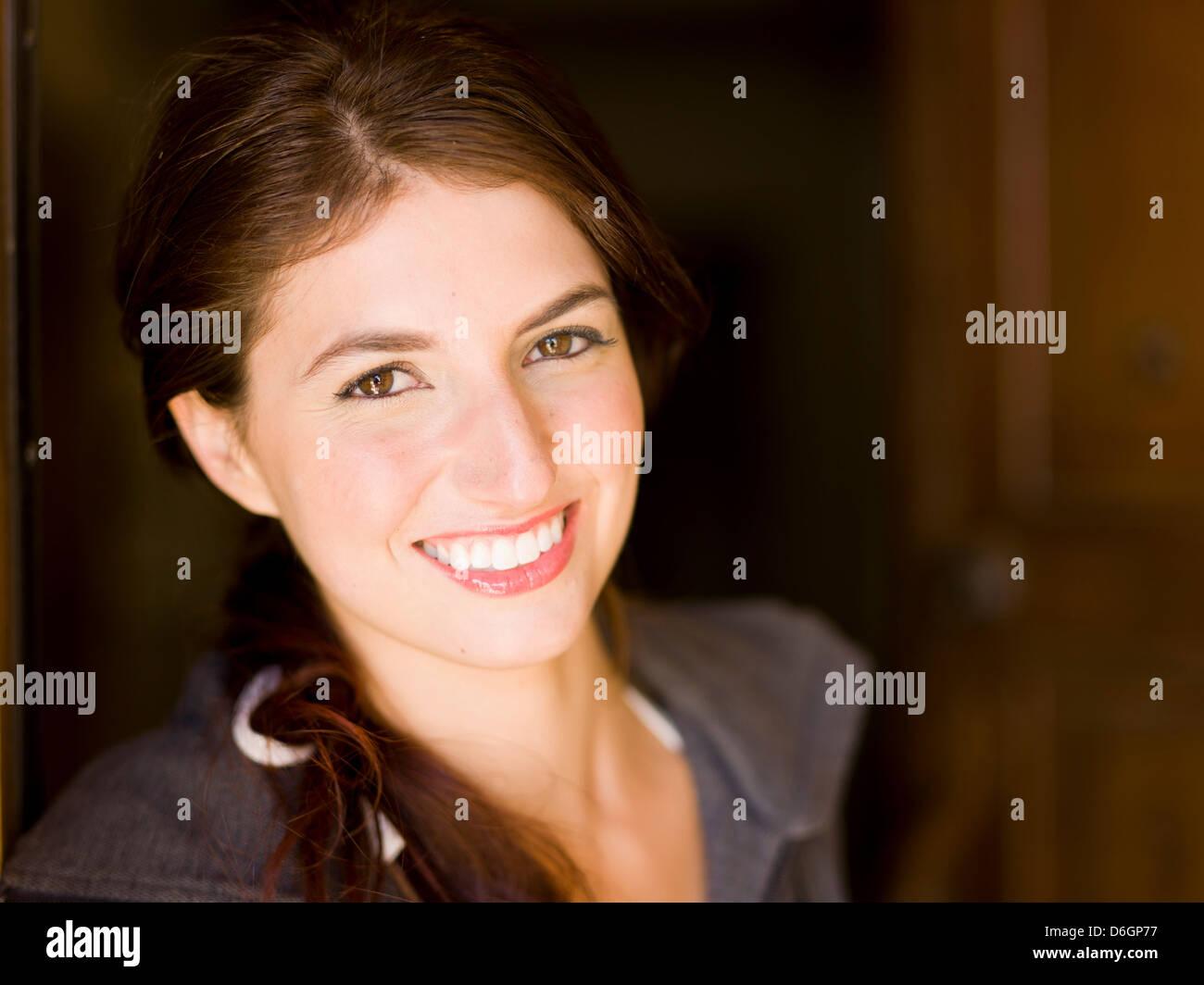 Smiling woman standing in doorway Photo Stock