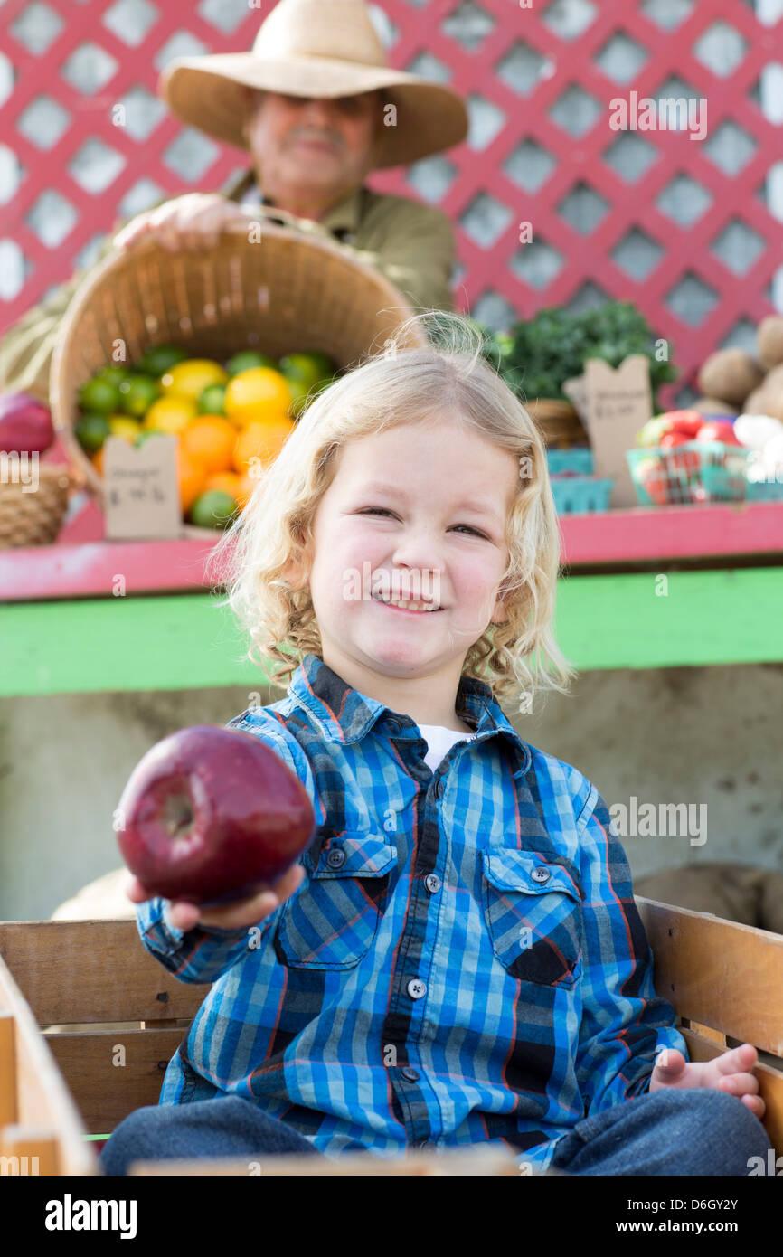 Boy holding apple au farmer's market Photo Stock