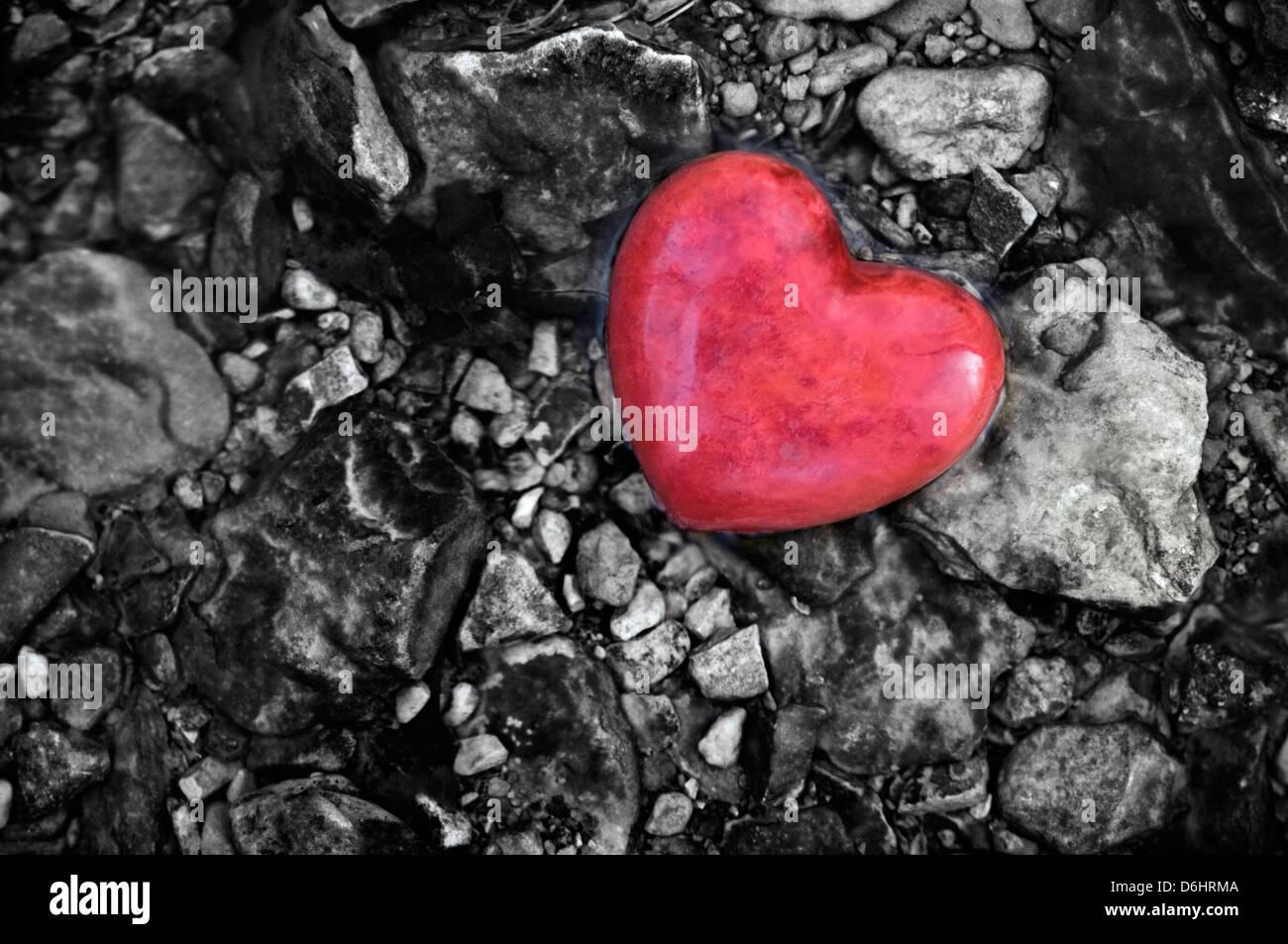 Coeur de pierre rouge au milieu de cailloux dans un ruisseau Photo Stock