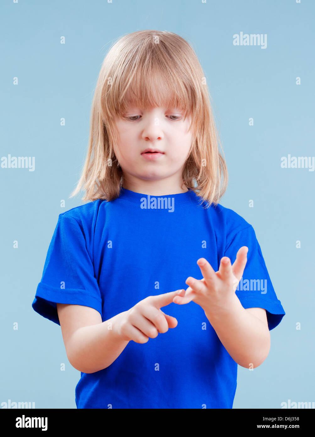 Garçon avec de longs cheveux blonds compte sur les doigts de la main - isolé sur bleu Photo Stock