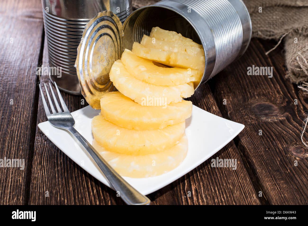 Ananas en conserve sur fond de bois Photo Stock