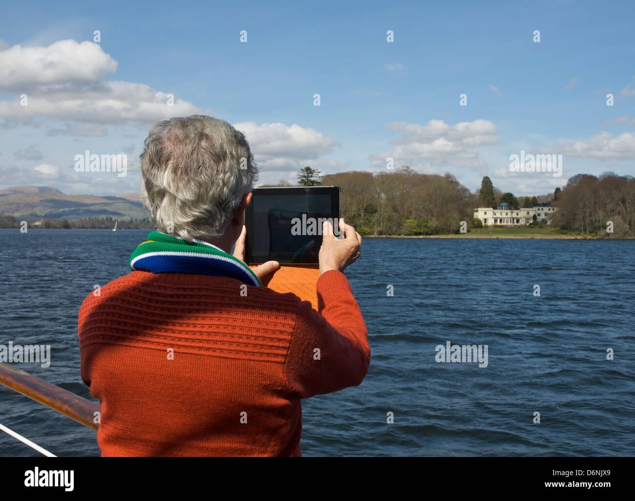 Man taking photograph avec son iPad, le lac Windermere, Parc National de Lake District, Cumbria, Angleterre, Royaume Photo Stock