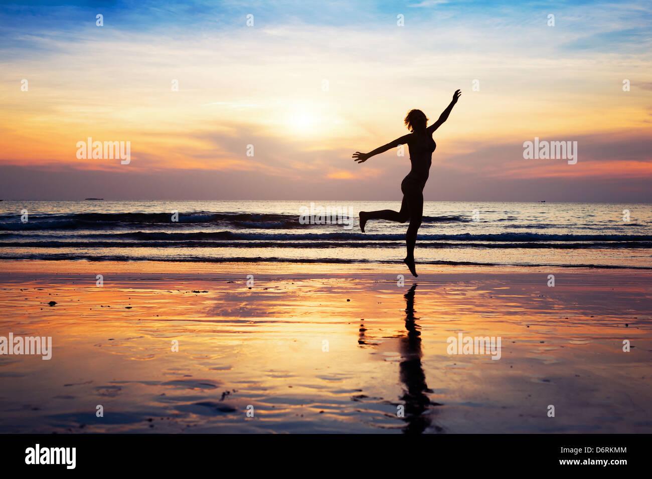 Silhouette de femme sautant sur la plage au coucher du soleil Photo Stock