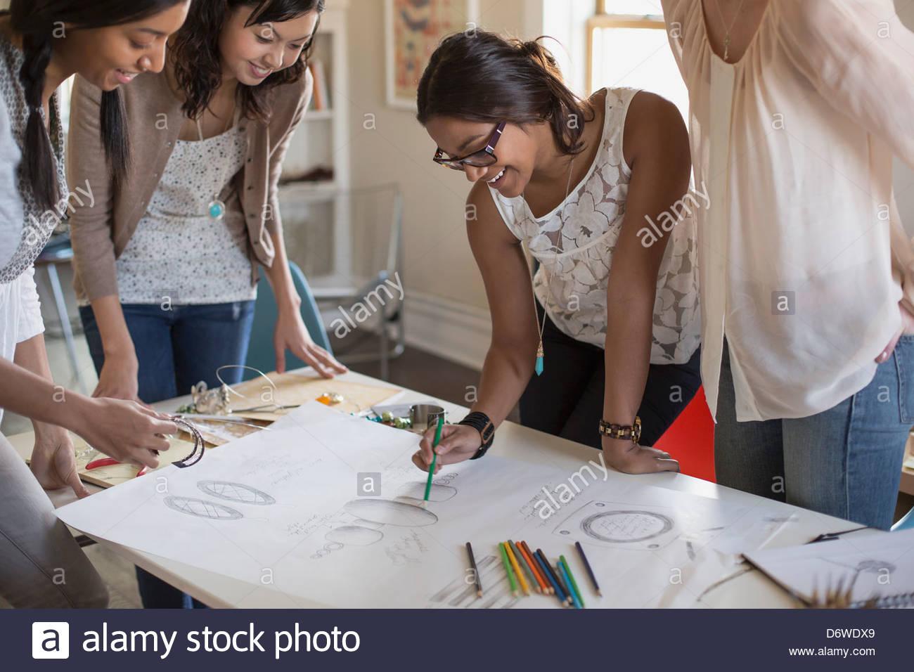 Dessin de conception de bijoux artiste féminine avec des collègues au bureau permanent Photo Stock