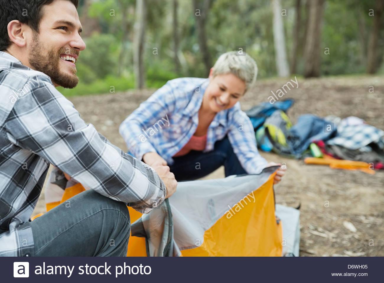Happy Mid adult man à l'écart lors de la configuration de tente avec femme Photo Stock