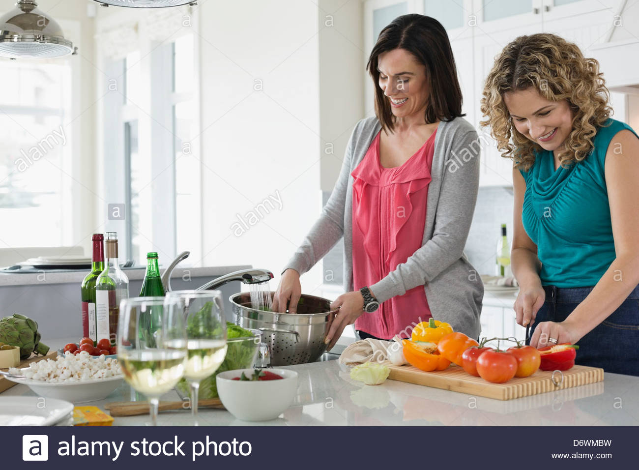 Mature Women cooking together in kitchen Photo Stock