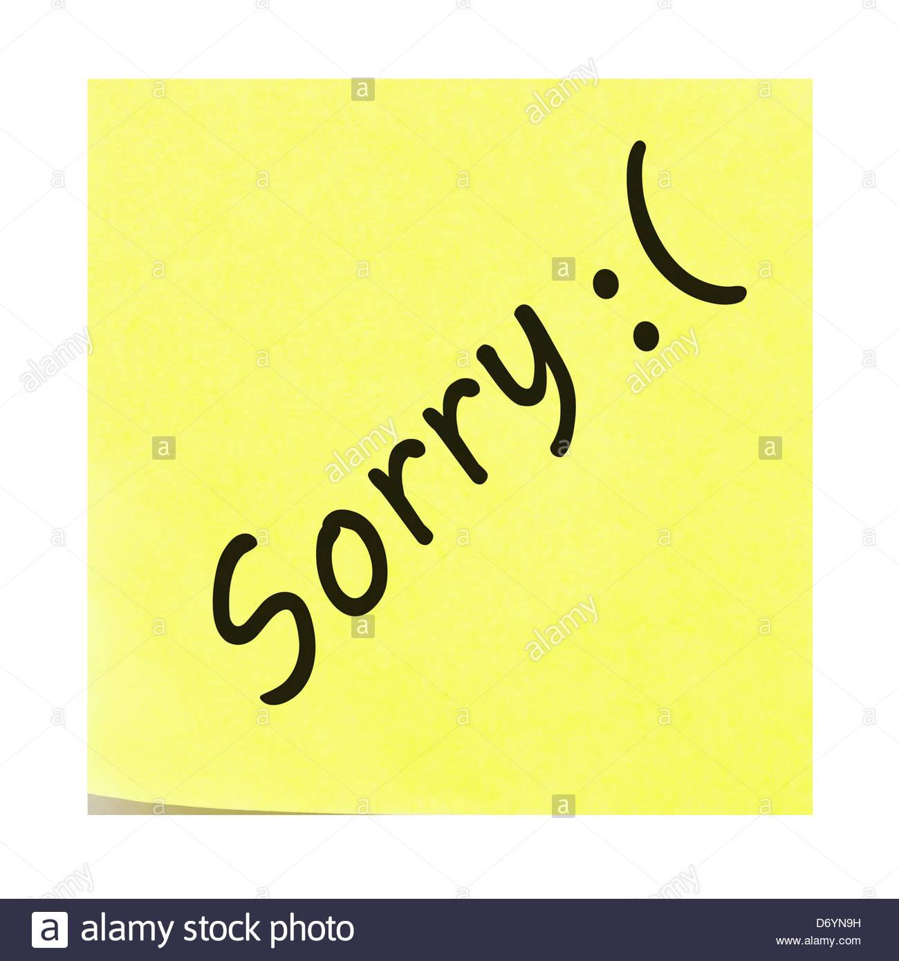 Désolé:( visage triste écrit sur un post-it jaune. Post-it avec l'angle de pelage. Photo Stock