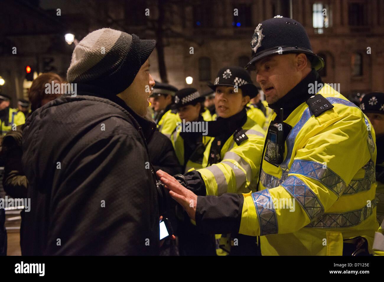 Metropolitan police tente de calmer un manifestant qui sent qu'il est détenue contre son gré Photo Stock