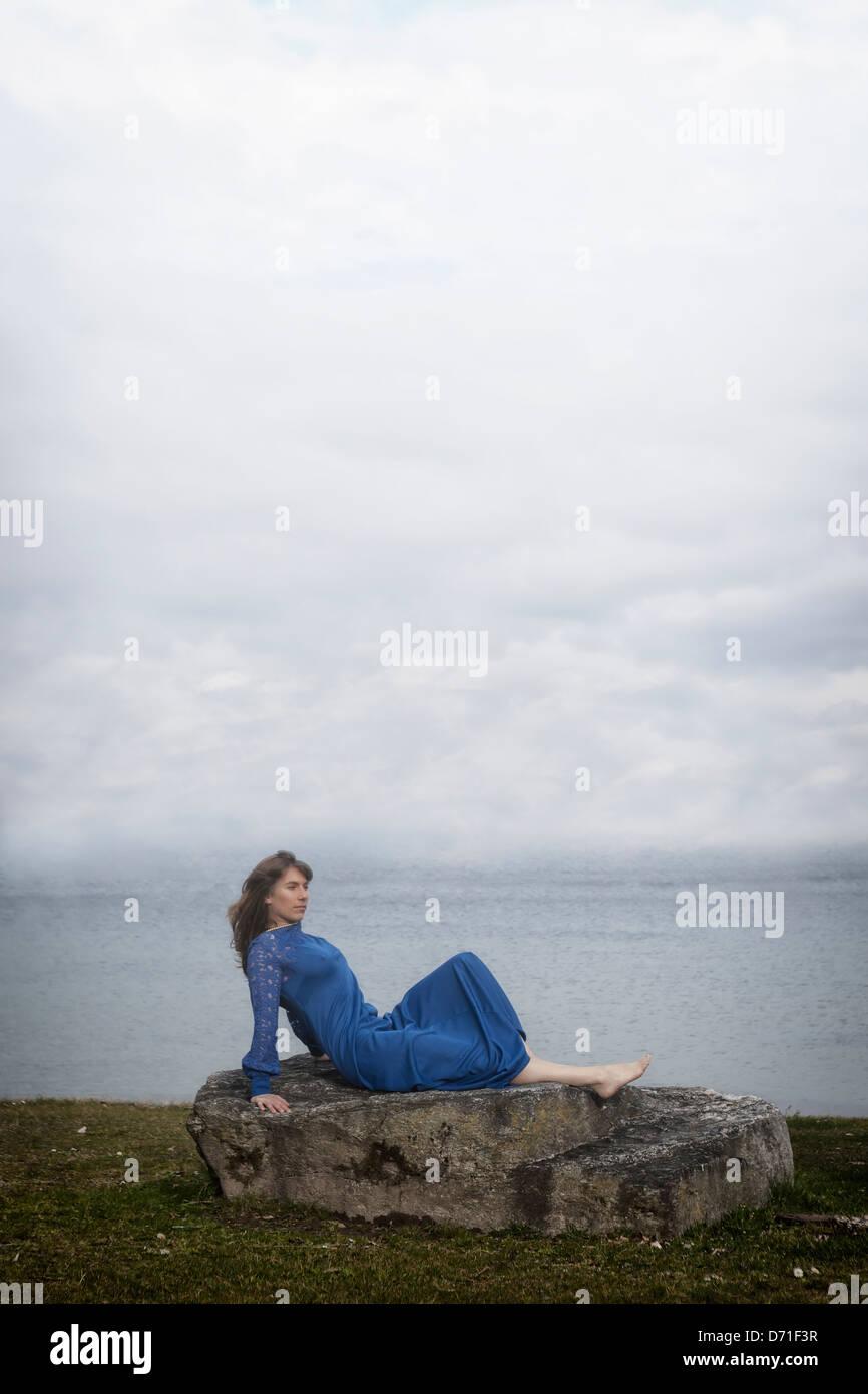 Une fille dans une robe bleue est couché sur une pierre Photo Stock
