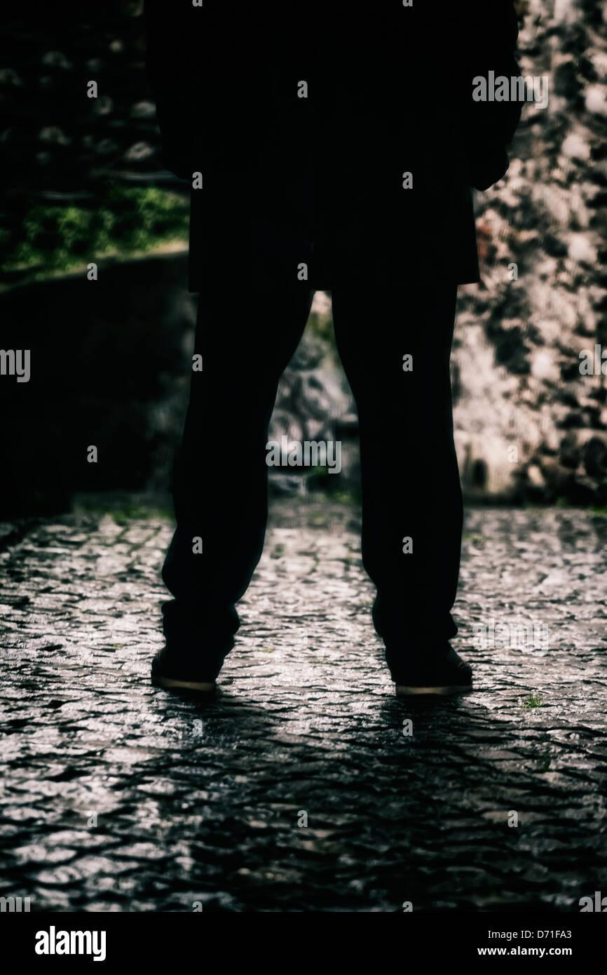 Les jambes d'un homme dans une ruelle sombre Photo Stock