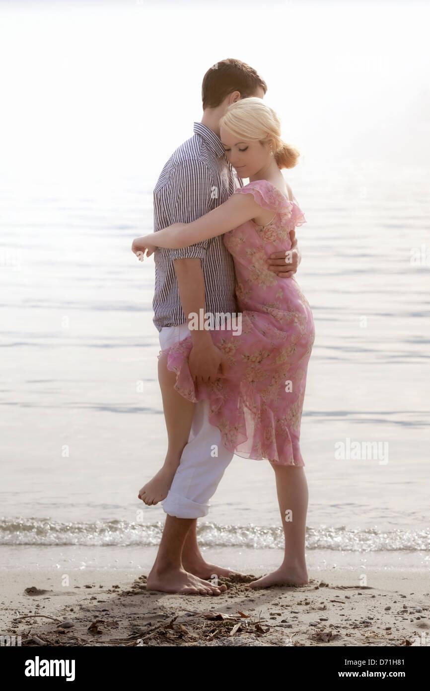 Un couple sur la plage, serrant les uns les autres Photo Stock