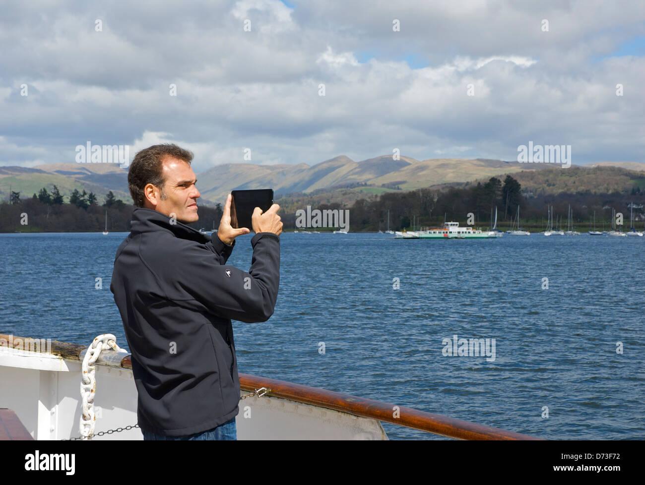 L'homme de prendre des photos avec son iPad, le lac Windermere, Parc National de Lake District, Cumbria, Angleterre, Photo Stock