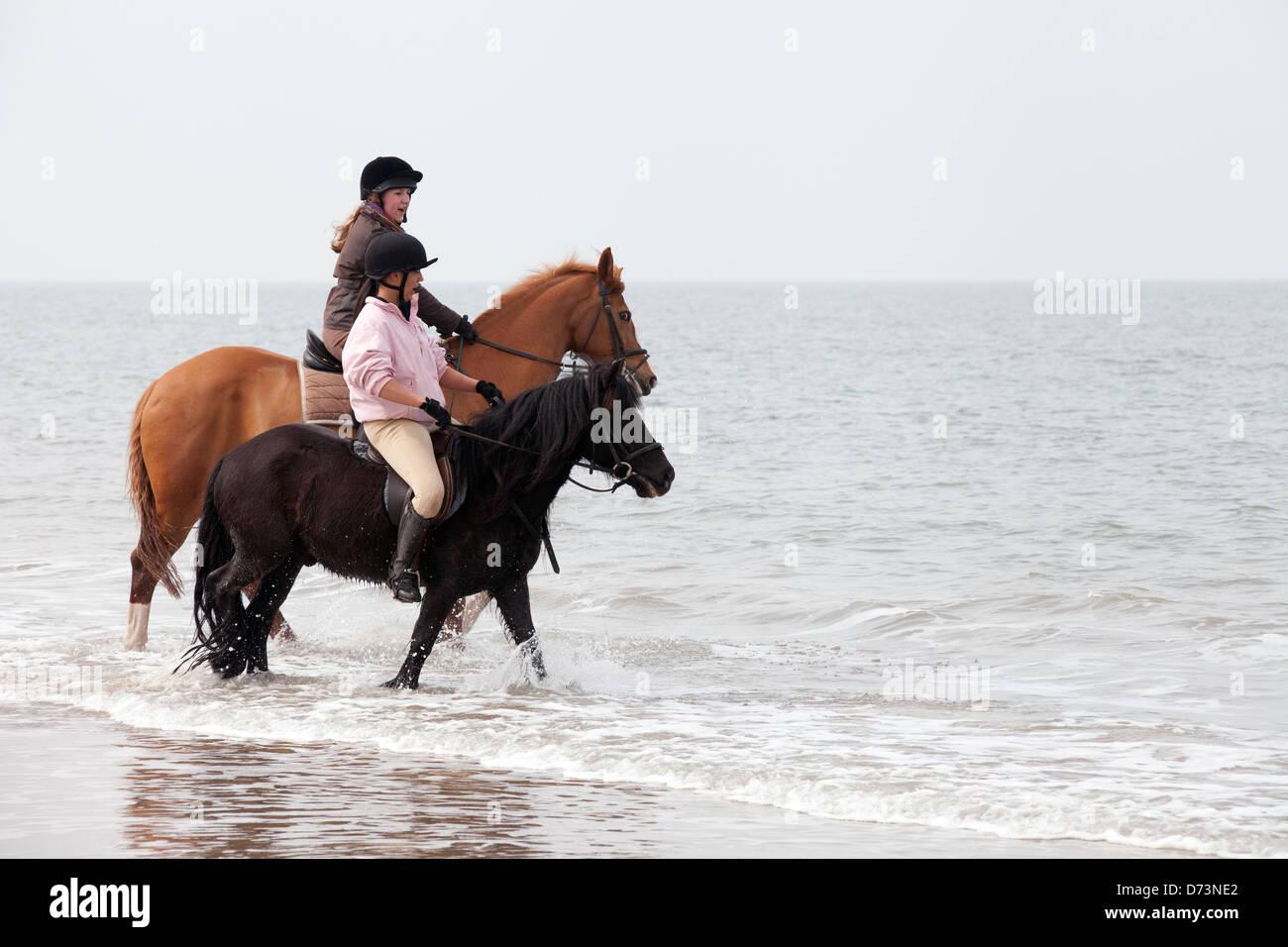 Deux jeunes femmes de l'équitation dans la mer surfez au bord de l'eau, Holkham Beach Norfolk, UK Photo Stock