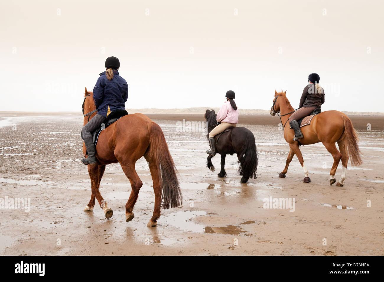 L'équitation UK - trois filles sur leurs chevaux, Holkham Beach, East Anglia, Angleterre Norfolk Photo Stock