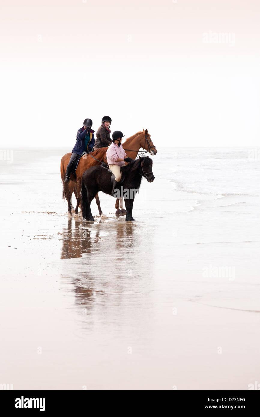 Trois femmes équitation sur Holkham Beach, Norfolk Coast, East Anglia, Royaume-Uni Photo Stock