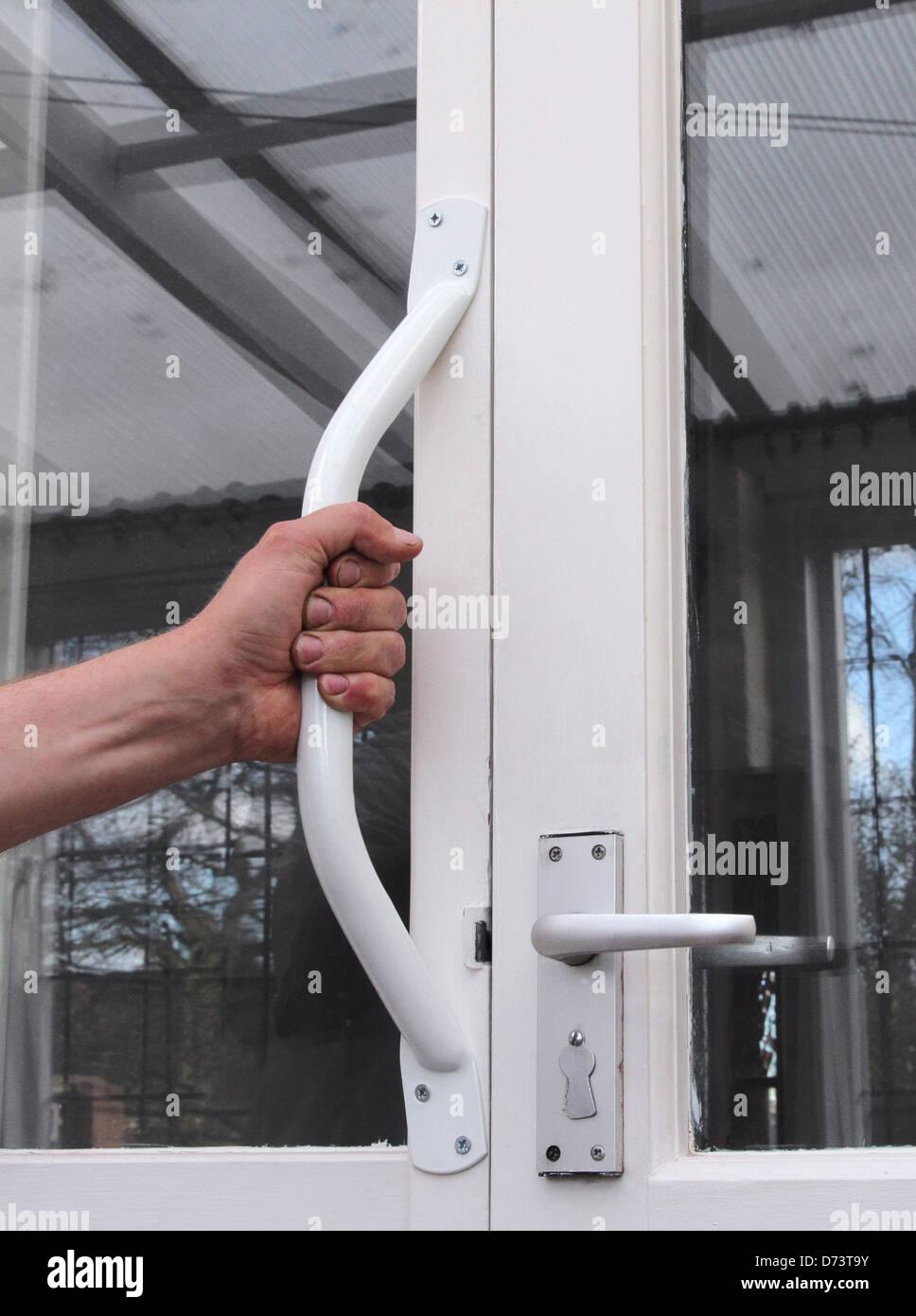 La main de l'homme en saisissant une poignée de l'invalidité, une forme de handicap vivant dans Photo Stock