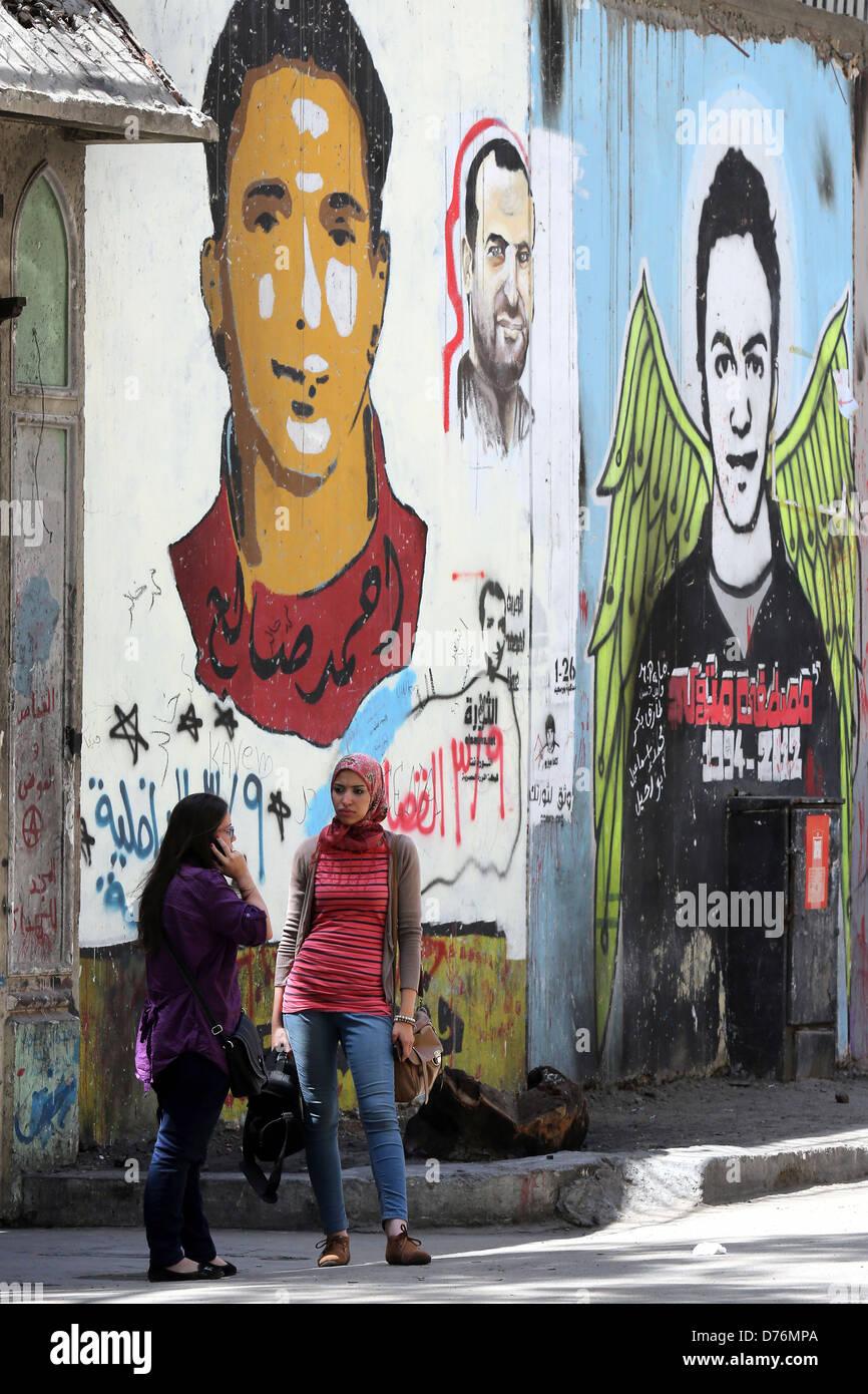 La femme en face d'une peinture murale révolutionnaire sur un mur des martyrs près de la place Tahrir Photo Stock