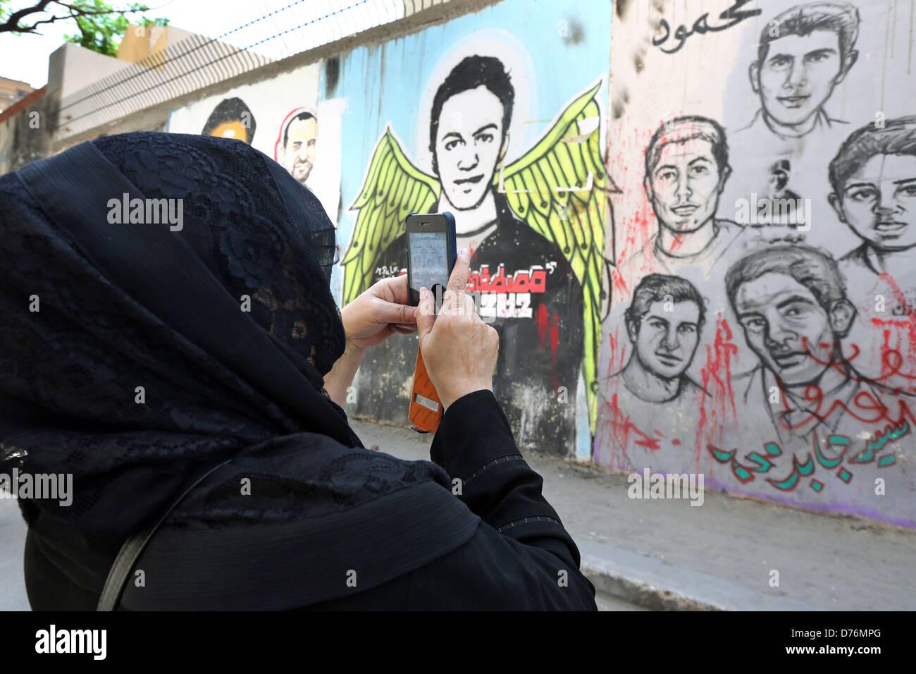 Femme prend des photos d'une fresque révolutionnaire sur un mur des martyrs près de la place Tahrir Photo Stock