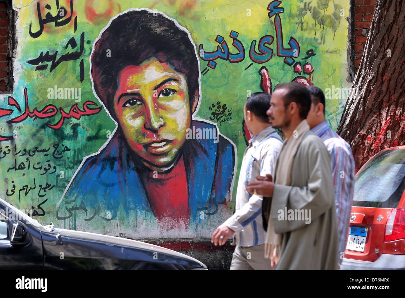 Les hommes marchant devant une fresque révolutionnaire sur un mur des martyrs près de la place Tahrir Photo Stock