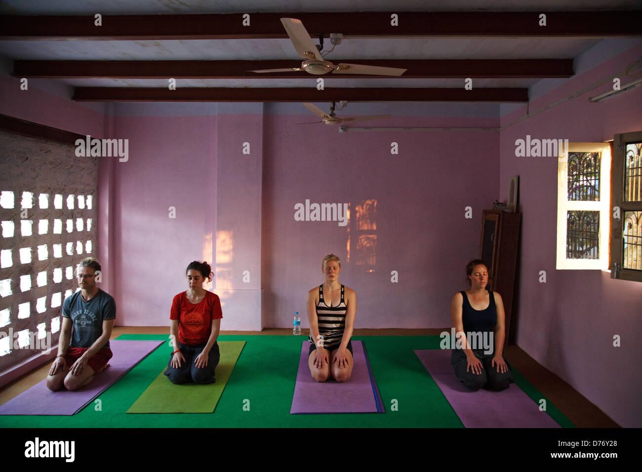 Les étrangers pratiquant le yoga dans une école de yoga à Varanasi, Inde. Photo Stock