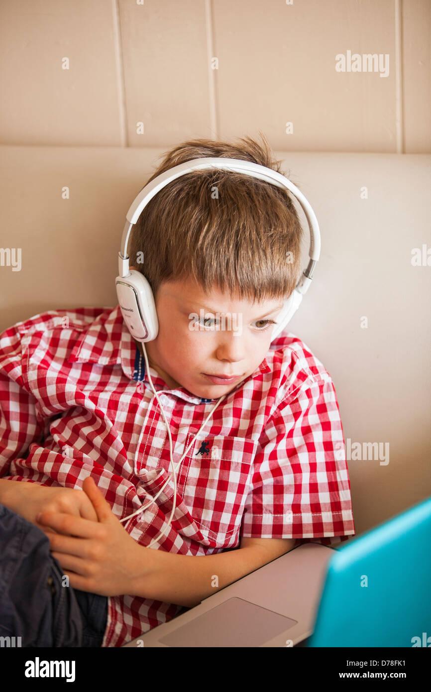 Boy using laptop et écouteurs Photo Stock