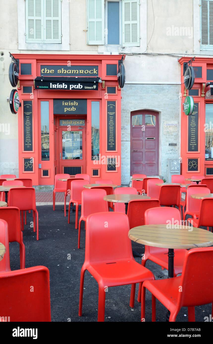 Irish Pub Bar Café de la chaussée ou avec des tables vides et des chaises rouges Vieux Port Marseille France Banque D'Images